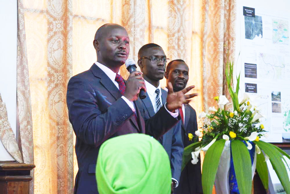 Dr Kenneth Ssemwogerere (L) addressing the guests while James (Centre) looks on