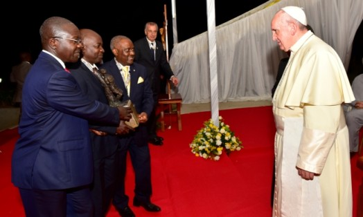 Prof. George Kyeyune-MTSIFA, CEDAT (2nd L) assisted by City Businessman-Mr. Yiga (L) and Rtn. Emmanuel Katongole-Quality Chemicals (3rd L) prepares to present a Bust of Uganda Martyr Anderea Kaggwa to Pope Francis during his visit to Munyonyo Shrine, Kampala Uganda on 27th November 2015 - See more at: http://news.mak.ac.ug/2015/12/how-prof-kyeyune%E2%80%99s-gifted-hands-got-him-pope-francis#sthash.NtBwp7Cy.dpuf